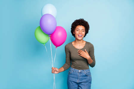 Portrait of positive cheerful mulatto girl hold baloons got for anniversary, have free time with friends listen funny jokes laugh wear green stylish jumper denim jeans isolated blue color background