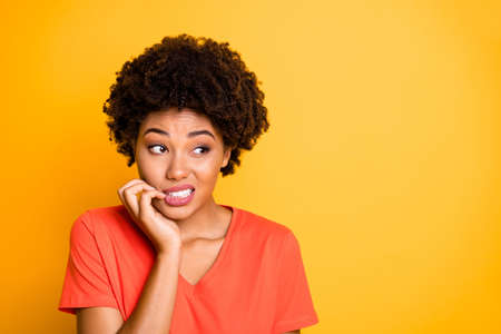 Copyspace photo of frightened afraid fearful woman biting her nails while, observing terrible stuff going on wearing orange t-shirt isolated over yellow vivid color background