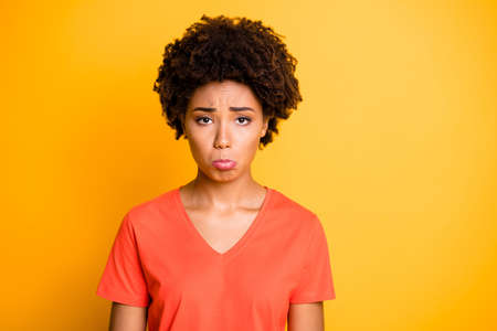 Photo of sullen dark skin lady offended after boyfriend rude behavior, wear orange v neck t-shirt isolated yellow color background