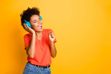 Copyspace photo of curly wavy cheerful charming lady singing into her imaginary, microphone wearing jeans denim wireless earphones isolated over yellow vibrant color background