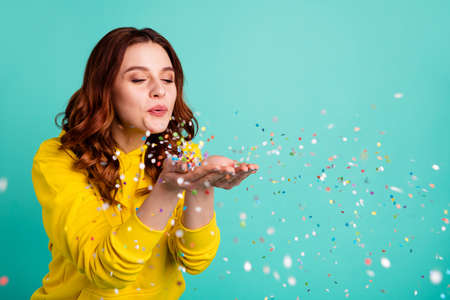 Photo of curly wavy trendy white cheerful charming sweet pretty youngster blowing confetti away from his hands palms enjoying pocess isolated over turquoise vibrant color background