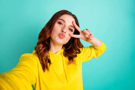 Photo of charming cute cheerful nice funky funny youngster taking selfie kissing you showing v-sign isolated over teal vibrant color background