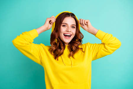 Photo of cheerful cute nice charming pretty sweet putting her hood on smiling toothily beaming isolated over teal vivid color background