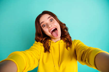 Photo of curly wavy charming nice cute sweet pretty girlfriend in trip showing you tongue out with overjoyed facial expression taking selfie in yellow sweater isolated over teal vivid color background