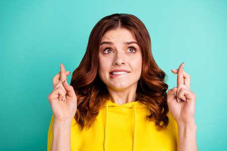 Foto eines stilvollen, trendigen, welligen, lockigen, ängstlichen Mädchens, das schlechte Laune erwartet und ein gelbes Pullover-Sweatshirt trägt, das sich auf die Lippen beißt, einzeln auf türkisfarbenem Hintergrund