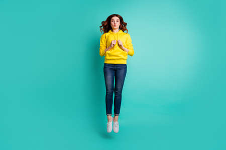 Full length body size photo of charming sweet pretty cute nice youngster kissing you through air while jumping up in jeans denim footwear isolated teal vibrant color background