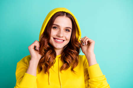 Close up photo of wavy cheerful cute nice charming trendy toothy youth putting sweater hood on isolated over vivid teal color background
