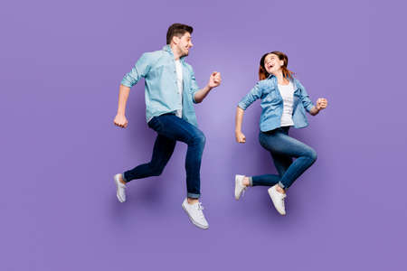 Full body photo of fun romantic funny brown hair redhair spouses jump run enjoy weekends holidays wear modern spring outfit white sneakers isolated over violet purple color background Stock fotó