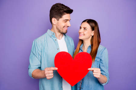 Portrait of romantic lovely spouses students hold paper card red big heart sign of their romance enjoy date 14-february holidays wear denim jeans shirt isolated over purple violet color background