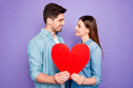 Profile side photo of romantic two students married couple hold paper card heart sign of feelings gift for 14-february honeymoon wear denim jeans outfit isolated over purple violet color background