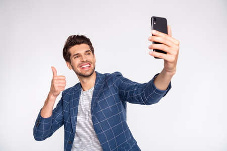 Portrait of his he nice attractive trendy stylish cheerful cheery glad businessman wearing blue checked blazer taking making selfie showing thumbup isolated over light white pastel background