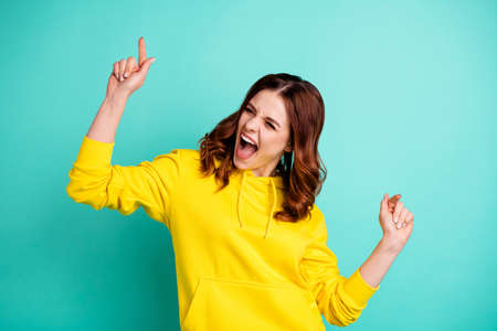 Photo of white cheerful attractive teenager screaming while dancing as discotheque wearing yellow clothes isolated over teal vibrant color background Stock Photo