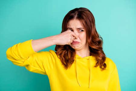 Foto di una ragazza disgustata che sente l'odore di qualcosa di brutto e che si chiude il naso isolata su uno sfondo di un vivido colore turchese
