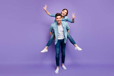 Full size photo of romantic couple with brunet hair redhair enjoy date honeymoon hug piggyback make v-signs wear trendy stylish outfit isolated over violet color background Stock Photo
