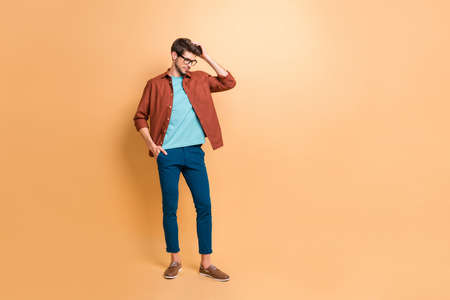 Full length body size view of his he nice attractive fashionable brunette guy hipster posing touching fixing hair isolated over beige color pastel background