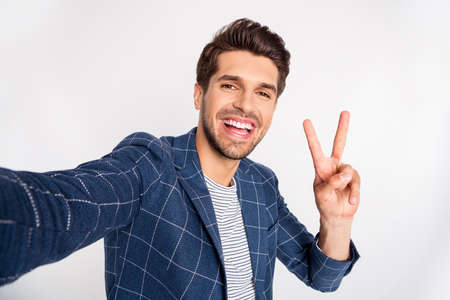 Self-portrait of his he nice attractive cheerful cheery glad delighted funny director executive manager wearing checked blazer showing v-sign isolated over light white pastel background Stock Photo