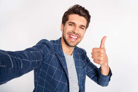 Self-portrait of his he nice attractive satisfied cheerful cheery glad director ceo boss chief wearing checked blazer showing thumbup isolated over light white pastel background