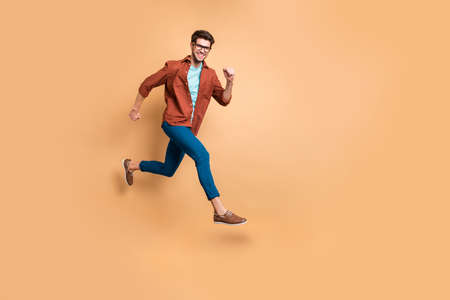 Full length body size view of nice attractive cheerful cheery strong sportive successful guy leader jumping in air running fast hurry-up meeting appointment isolated over beige color pastel background