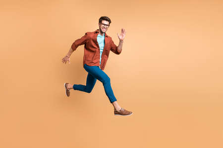 Full length body size view of his he nice attractive cheerful cheery glad active successful guy leader jumping in air running fast hurry-up meeting isolated over beige color pastel background