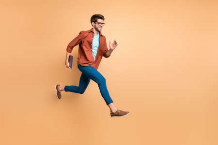 Full length body size view of his he nice attractive cheerful glad guy leader jumping in air carrying laptop running fast late hurry-up meeting appointment isolated over beige color pastel background