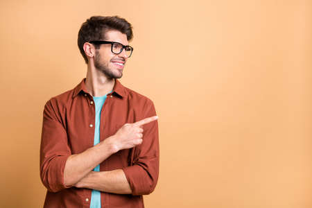 Close-up portrait of his he nice attractive cheerful cheery glad content brunet guy pointing forefinger aside copy space advice advert ad decision isolated over beige color pastel background Standard-Bild - 131313489