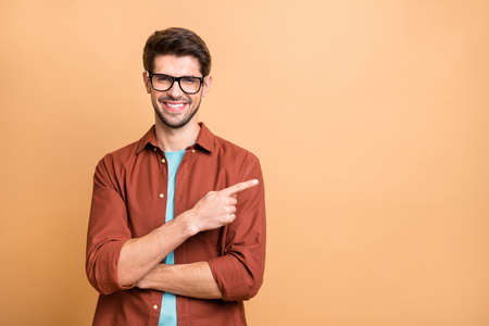 Close-up portrait of his he nice attractive cheerful cheery glad successful content brunet guy pointing forefinger aside advice advert solution isolated over beige color pastel background Standard-Bild - 131313175