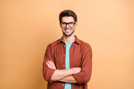 Close-up portrait of his he nice attractive content successful cheerful cheery brown-haired guy professional financier expert shark folded arms isolated over beige color pastel background
