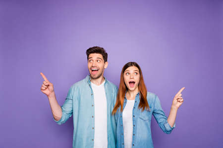 Portrait of excited romantic couple student scream omg wow look at copyspace point index finger show ads recommendation wear lifestyle clothes isolated over purple violet color background