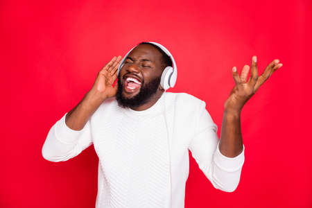 Photo of amazing dark skin man listening to favorite playlist in earflaps crazy singing cool track wear white knitted sweater isolated red background