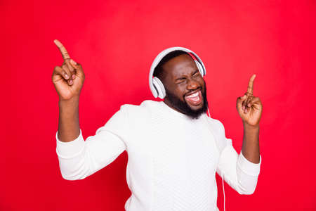 Foto van een geweldige man met een donkere huid die favoriete afspeellijst in oorkleppen luistert, geniet van het beste liedmomentritme, draag een witte gebreide trui, geïsoleerde rode achtergrond