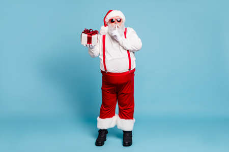 Full length photo of funny funky fat modern santa claus with big belly show index finger, speechless sign hold gift box want give wish for eve wear red cap suspenders isolated blue color background