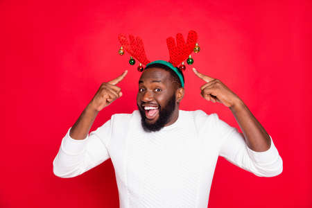 Portrait of amazed surprised brown hair crazy black skin man point at rudolf deer horns enjoy his accessory for christmas eve party celebration wear white pullover isolated red color background