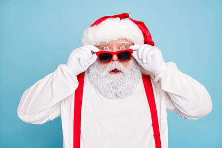 Close up photo of impressed fat overweight santa claus stare in modern eyeglasses look funny funky hear wonder christmas seasonal discounts wear suspenders overalls isolated over blue color, background