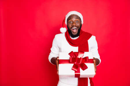Wow its for me. Portrait of excited african man in santa claus cap hold big package get present for newyear celebration party from his friend wear style jumper isolated over red color background Foto de archivo