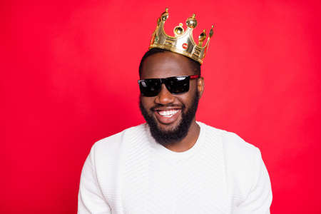 Portrait of positive cool afro american brown hair beard guy millionaire in eyewears look feel arrogant egocentric wear gold diadem king style clothes isolated over red color background