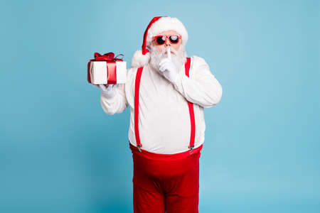 Hush its secret. Portrait of focused funny funky fat santa claus with big abdomen belly prepare gift for eve noel hold small giftbox, wear red pants suspenders isolated over blue color background