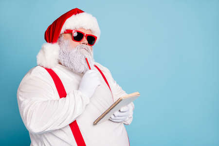 Close up photo of focused funny funky fat santa claus hold notebook, think about wish list plan decide what choose look thoughtful wear stylish trendy suspenders isolated over blue color background Stockfoto - 131459247