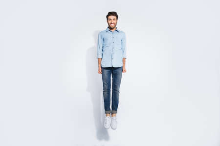 Full length photo of funny arabian guy jumping high rejoicing energetic sportive mood wear casual denim shirt isolated white color background
