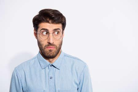 Photo d'un mec indien incroyable à côté de l'espace vide se sentir coupable pour une situation horrible porter des spécifications chemise en jean décontractée fond de couleur blanc isolé