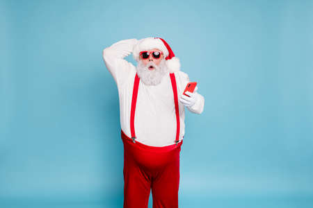 Portrait of funny funky fat modern santa claus in sunglass use his cell phone got christmas time blogs notification scream wow omg wear red suspenders, overalls isolated over blue color background
