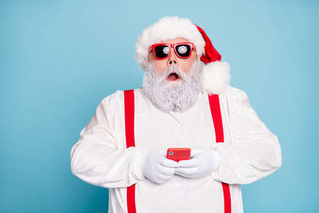 Close up photo of amazed funny funky overweight white hair long bearded santa claus, hipster use cell phone search winter discount text sms wear red suspenders isolated over blue color background