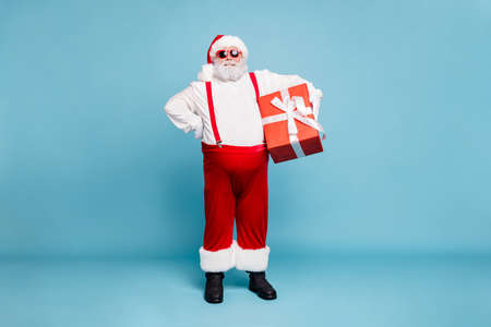 Full body photo of funny funky fat christmas father with big belly abdomen, hold gift box for noel follow newyear tradition spirit wear overalls red pants boots isolated over blue color background