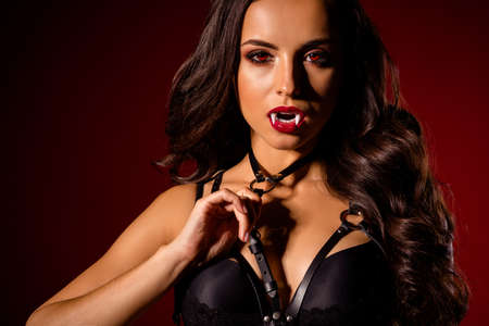 Cropped close-up view portrait of attractive stunning alluring enticing dominant black brunette wavy-haired lady vamp tightening harness isolated on dark red maroon burgundy marsala color background