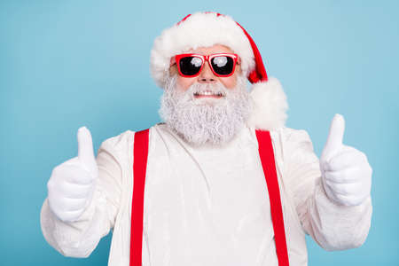 Close up photo of funny funky overweight santa claus in modern spectacles show thumb up sign recommend x-mas season sales wear white overalls red suspenders isolated over blue color background