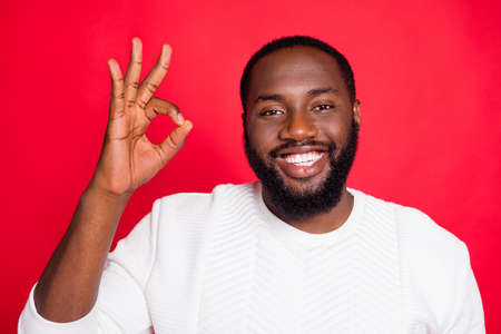 Close up photo of positive emotion cool dark skin man show ok sign recommend promo ads choose decide promotion wear trend outfit isolated over red color background