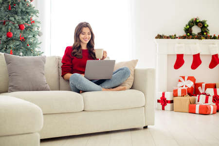 Photo of resting relaxing cozy cheerful girlfriend beautiful attractive charming watching something in her laptop enjoyed christmas atmosphere