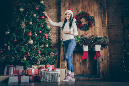 Full body photo of positive cheerful brown hair girl prepare for x-mas time party celebration decorate christmas tree with balls toys in house with newyear decoration garlands ornaments indoors