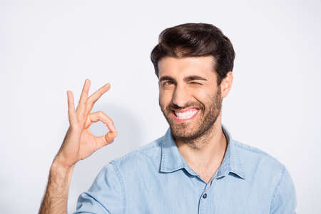 Photo of nice multiethnic handsome guy showing okey symbol approving good quality of product winking eye wear casual denim shirt isolated white color background Stock fotó
