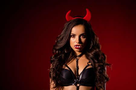 Nahaufnahmeporträt von ihr, sie ist eine schöne, attraktive, bezaubernde, bezaubernde, schwarze, brünette, gewellte Dame Diablo, die Höllendämonenhörner trägt, einzeln auf dunkelrotem kastanienbraunem Burgunder-Marsala-Farbhintergrund