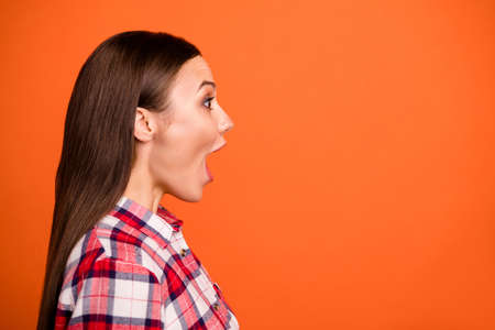 Profile side view close-up portrait of her she nice attractive pretty cheerful straight-haired girl wearing checked shirt opened mouth isolated on bright vivid shine vibrant orange color background